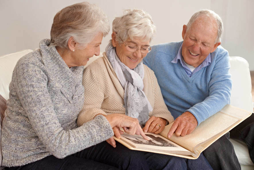 Three seniors sitting together looking at a picture album