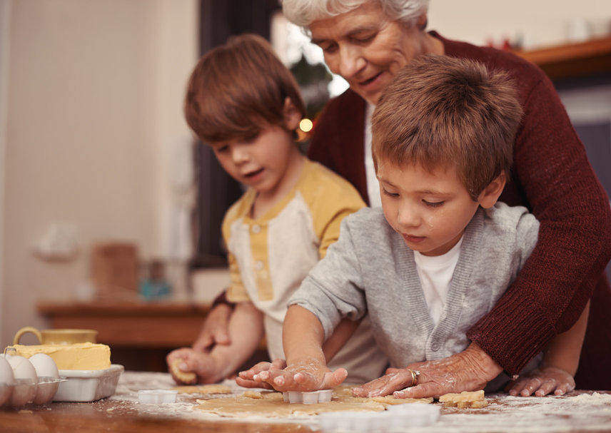Grandmother baking cookies with two grandsons