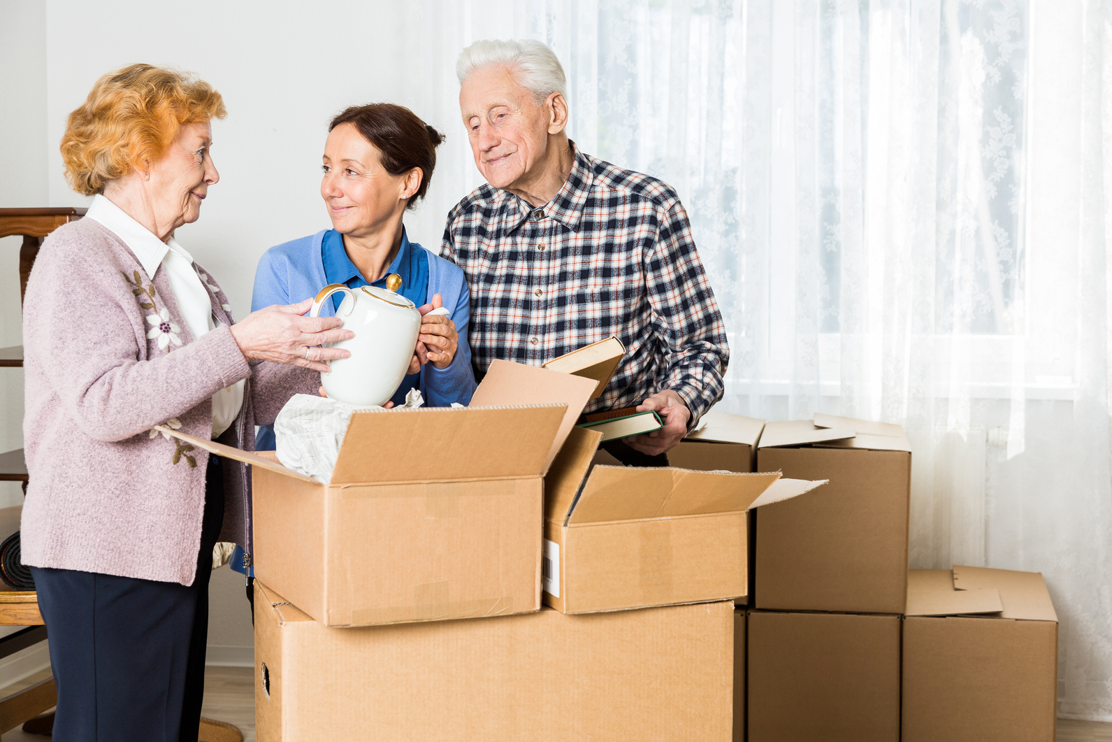 Three people looking at items as they downsize and move things into boxes