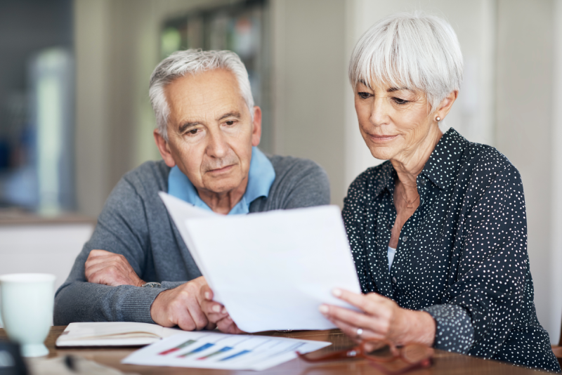 Senior couple reviewing financial documents to plan for retirement
