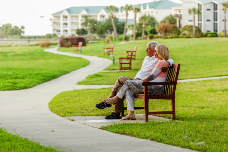 Elderly, retired couple sitting on a bench outside a retirement community on a sunny day in Florida