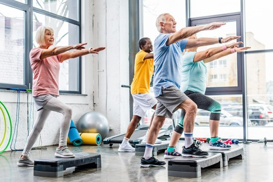 Senior fitness group spending onto platforms with arms outstretched forward