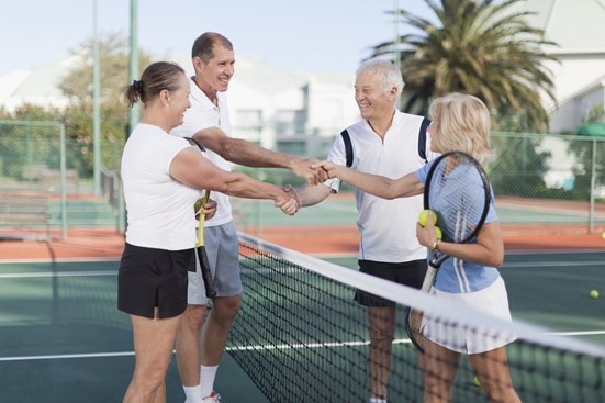 Senior couple shaking hands with another couple on a tennis court