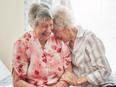 Two elderly women laughing together while sitting down